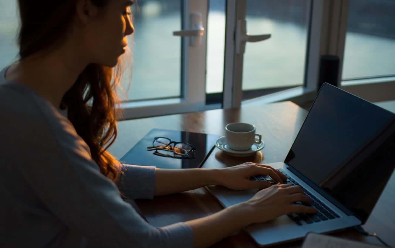 femme écrivant sur un ordinateur